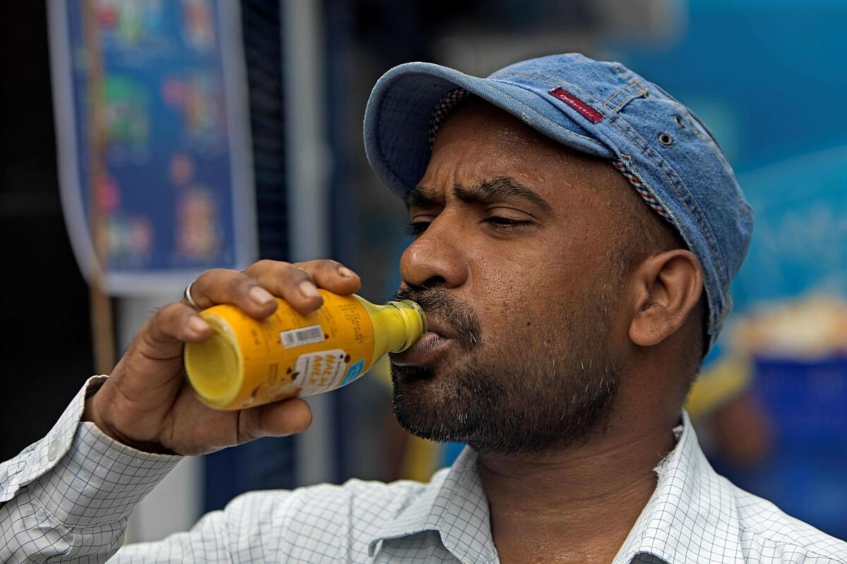 Một khách hàng uống sữa nghệ, sản phẩm có tên Haldi Milk từ công ty Mother Dairy, như một biện pháp phòng ngừa chống dịch Covid-19.  Ảnh: AFP