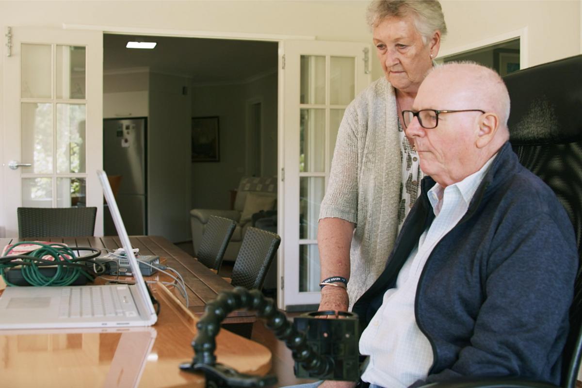 Graham Felstead, bệnh nhân đầu tiên được cấy thiết bị Stentrode, đang sử dụng để vận hành máy tính trong khi  Nancy, vợ ông đứng bên cạnh theo dõi. Ảnh: WSJ