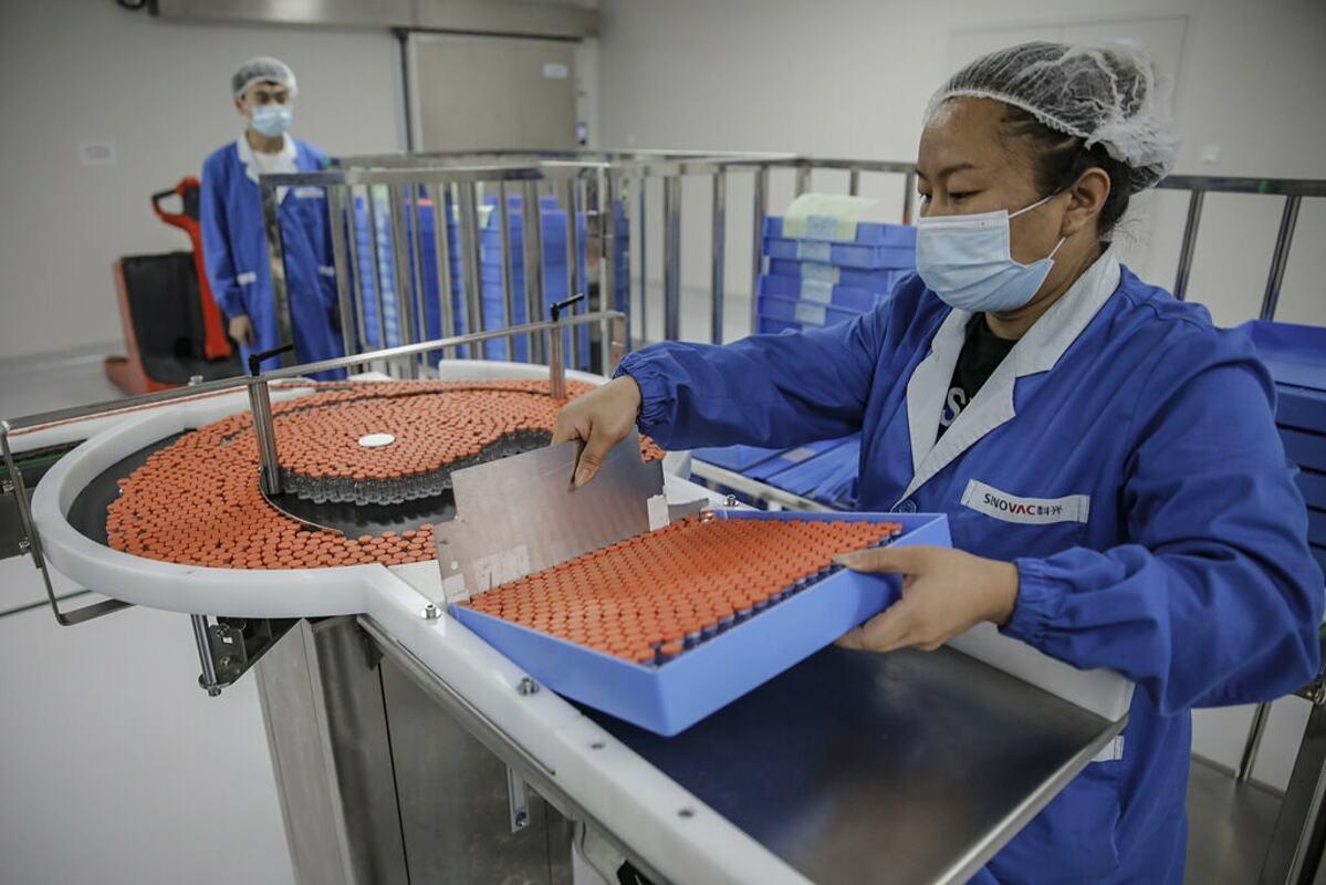 Nhân viên hãng dược SinoVac đang làm việc trong dây chuyền sản xuất vaccine. Ảnh: EPA