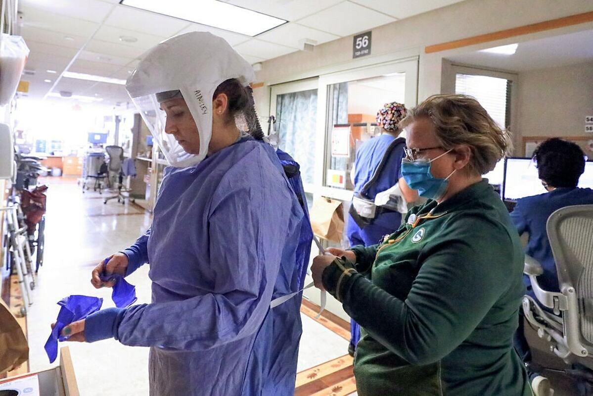 Nhân viên y tế tại một bệnh viện ở Madison đang mặc đồ bảo hộ để bước vào khu điều trị người mắc Covid-19. Ảnh: NY Times