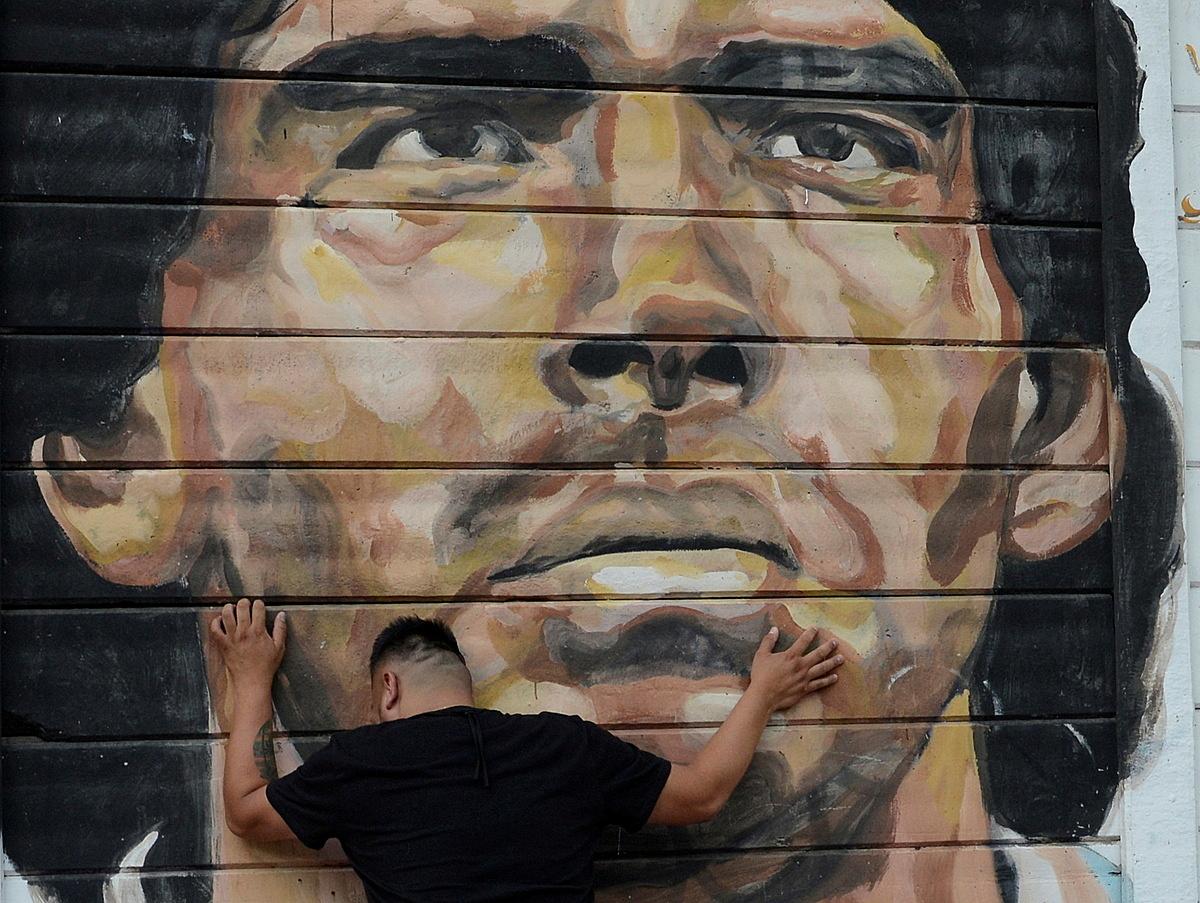 Một người hâm mộ gục đầu khi nghe tin Maradona qua đời, bên ngoài sân vận động mang tên ông ở Buenos Aires. Ảnh: Reuters.