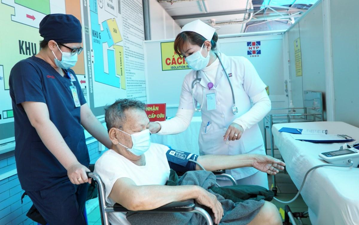 Nhân viên y tế đo nhiệt độ, hỗ trợ khai báo y tế cho bệnh nhân ưu tiên tại buồng sàng lọc riêng, Bệnh viện Nguyễn Tri Phương. Ảnh:Thư Anh.
