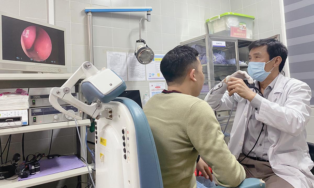 Bác sĩ Thành đang nội soi kiểm tra họng cho bệnh nhân. Ảnh: Thùy An