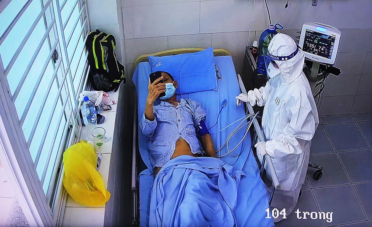 Bệnh nhân 1405 tỉnh táo, xem điện thoại. Ảnh: Phương Thảo.