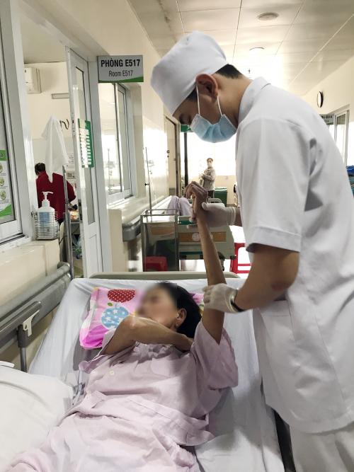 Kỹ thuật viên phục hồi chức năng đang tập vận động cho bệnh nhân. Ảnh: Lê Hồng Tuấn.