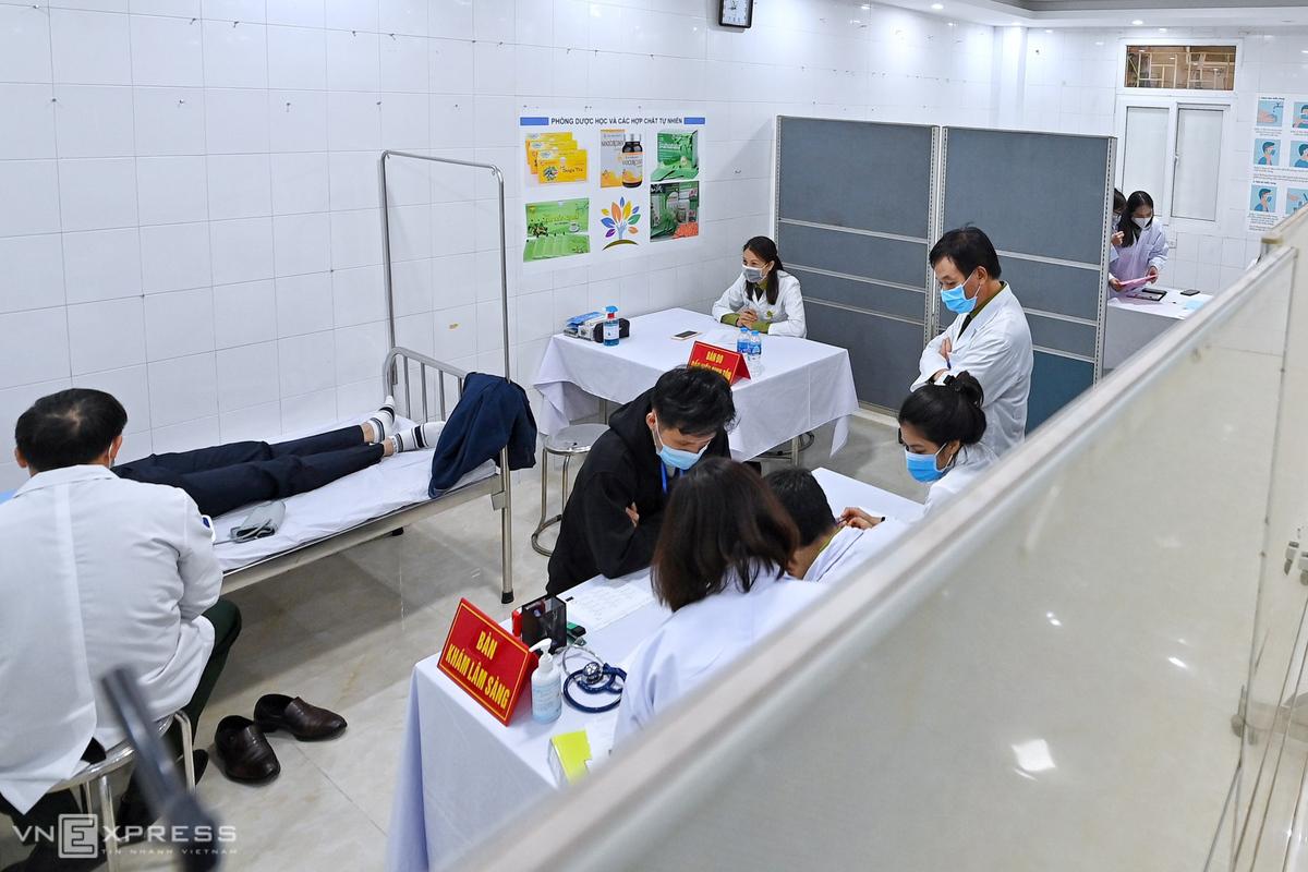 Các nhân viên y tế của Học viện Quân y tư vấn và khám sức khỏe cho các tình nguyện viên bên trong phòng kín. Ảnh: Giang Huy.
