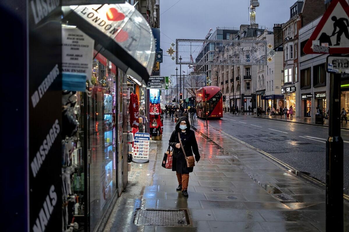 Người dân London đeo khẩu trang, đi lại trên đường phố vắng vẻ trong ngày đầu tiên thành phố áp đặt lệnh hạn chế cấp độ 3. Ảnh: NY Times