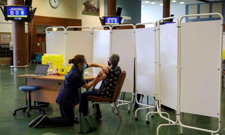Nhân viên y tế tiêm vaccine Covid-19 tại trung tâm tiêm chủng ở hạt Surrey, Anh hôm 16/12. Ảnh:Reuters.