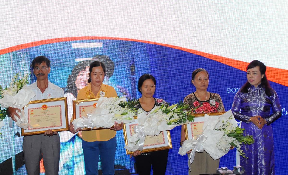 Cựu Bộ trưởng Bộ Y tế Nguyễn Thị Kim Tiến (bìa phải) trao Kỷ niệm chương Vì sức khoẻ nhân dân cho người mẹ (thứ hai từ phải qua) và các gia đình có người hiến tạng, trong lễ vinh danh năm 2016. Ảnh: Bác sĩ cung cấp.