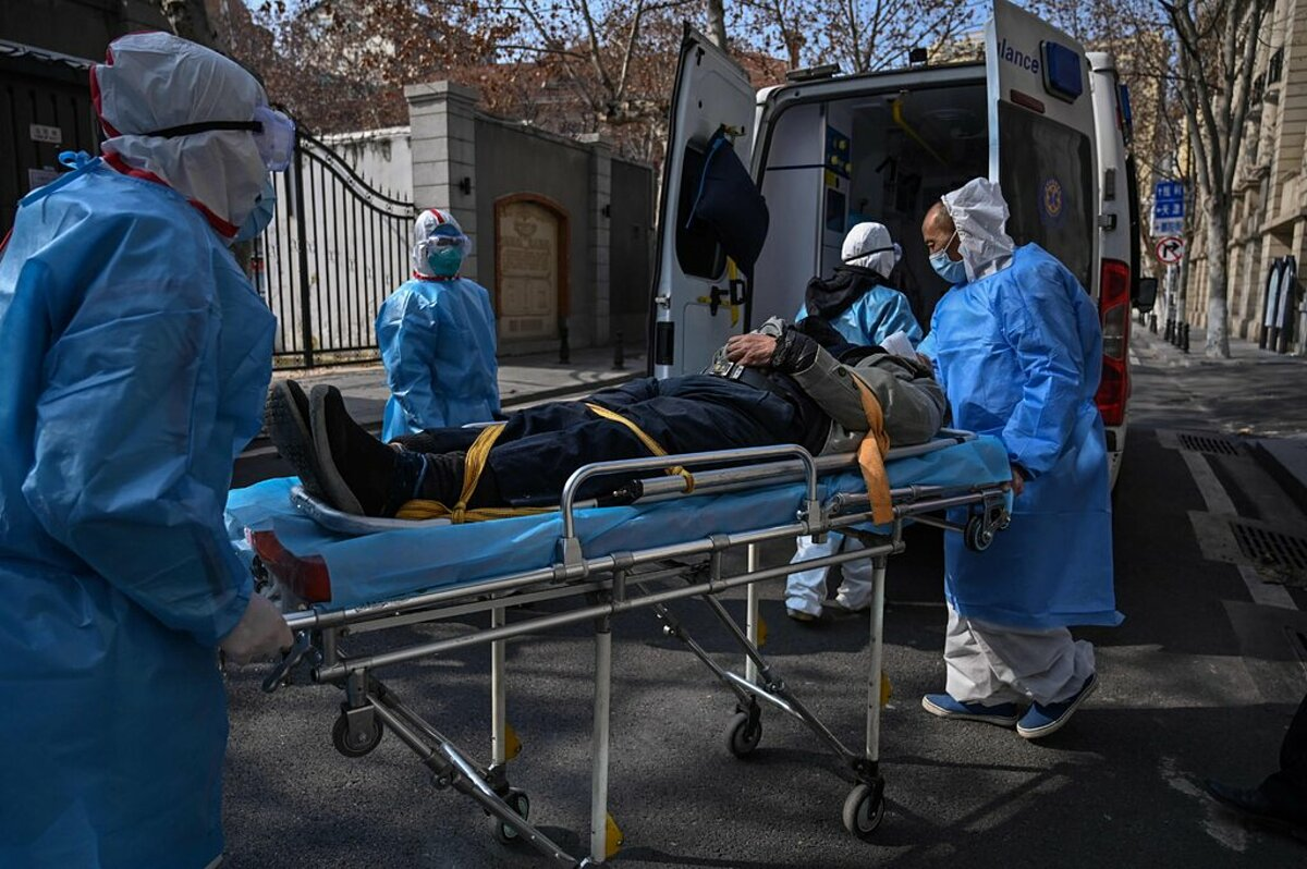 Wuhan medical staff bring a Covid-19 patient to the hospital, January 2020.  Photo: AFP