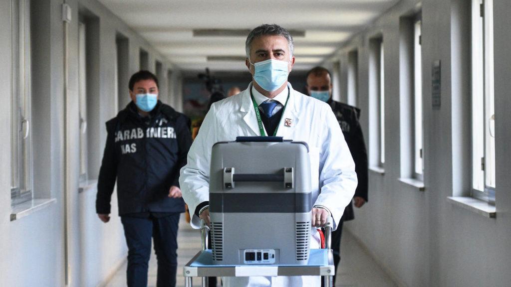 Cảnh sát hộ tống bác sĨ Andrea Machiavelli, Bệnh viện Cremona, khi ông đẩy xe chở thùng chứa vaccine Covid-19, hôm 26/12. Ảnh:AFP