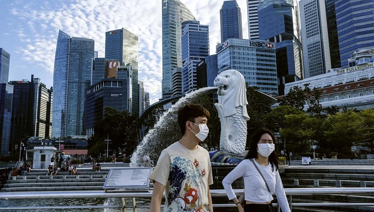 Một cặp đôi đeo khẩu trang đi dạo qua tượng Merlion ở Singapore. Ảnh: AP
