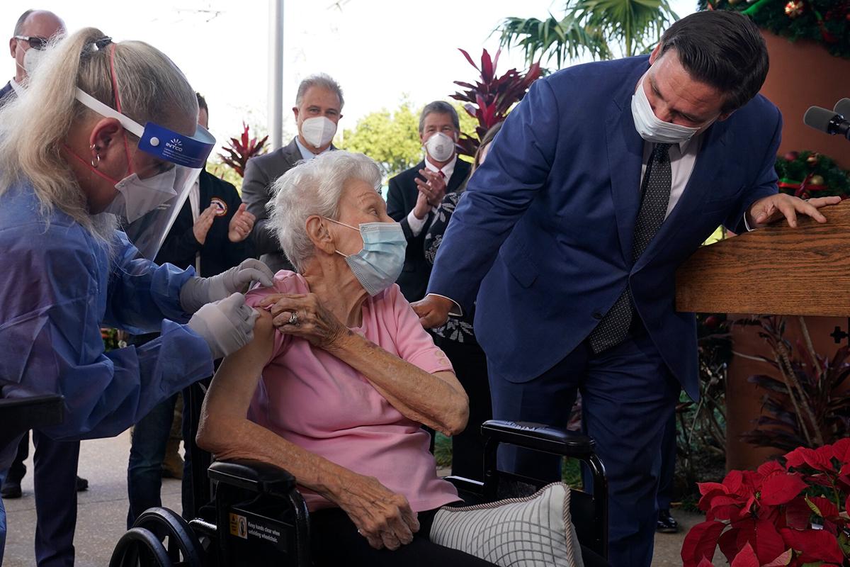 Thống đốc Ron DeSantis của Florida, phải, trong khi tiêm chủng tại nhà dưỡng lão Làng John Knox ở Bãi biển Pompano, Fla.