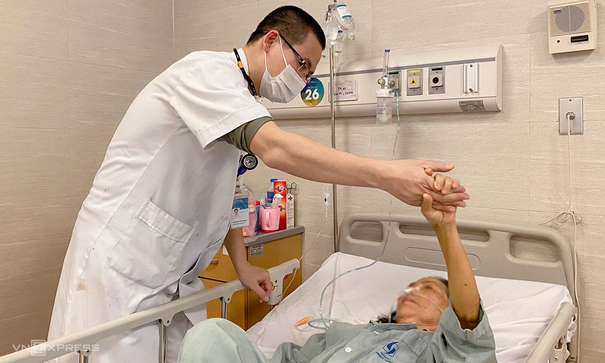 Bác sĩ Thắng yêu cầu bệnh nhân đưa cao tay, kiểm tra mức độ tỉnh táo của bệnh nhân trước khi cho bệnh nhân xuất viện. Ảnh: Thùy An