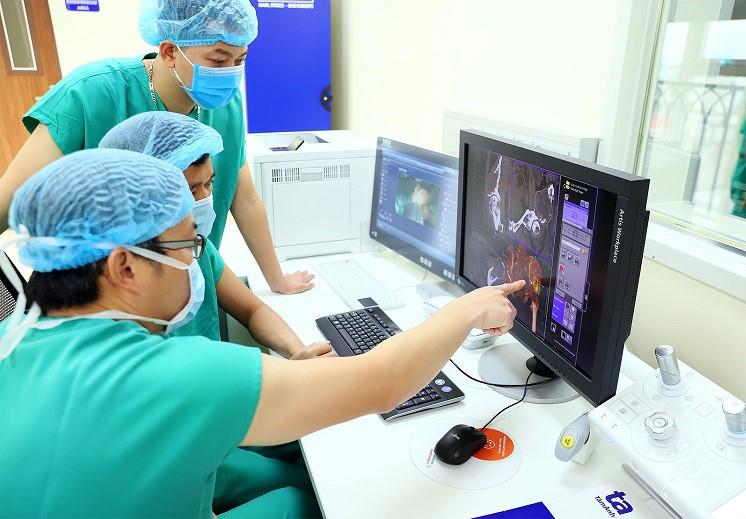 Bác sĩ phẫu thuật trao đổi về mô hình 3 chiều kỹ thuật số trên máy tính ngay tại khu điều khiển trong phòng mổ hybrid hiện đại. Ảnh: Bệnh viện Đa khoa Tâm Anh.