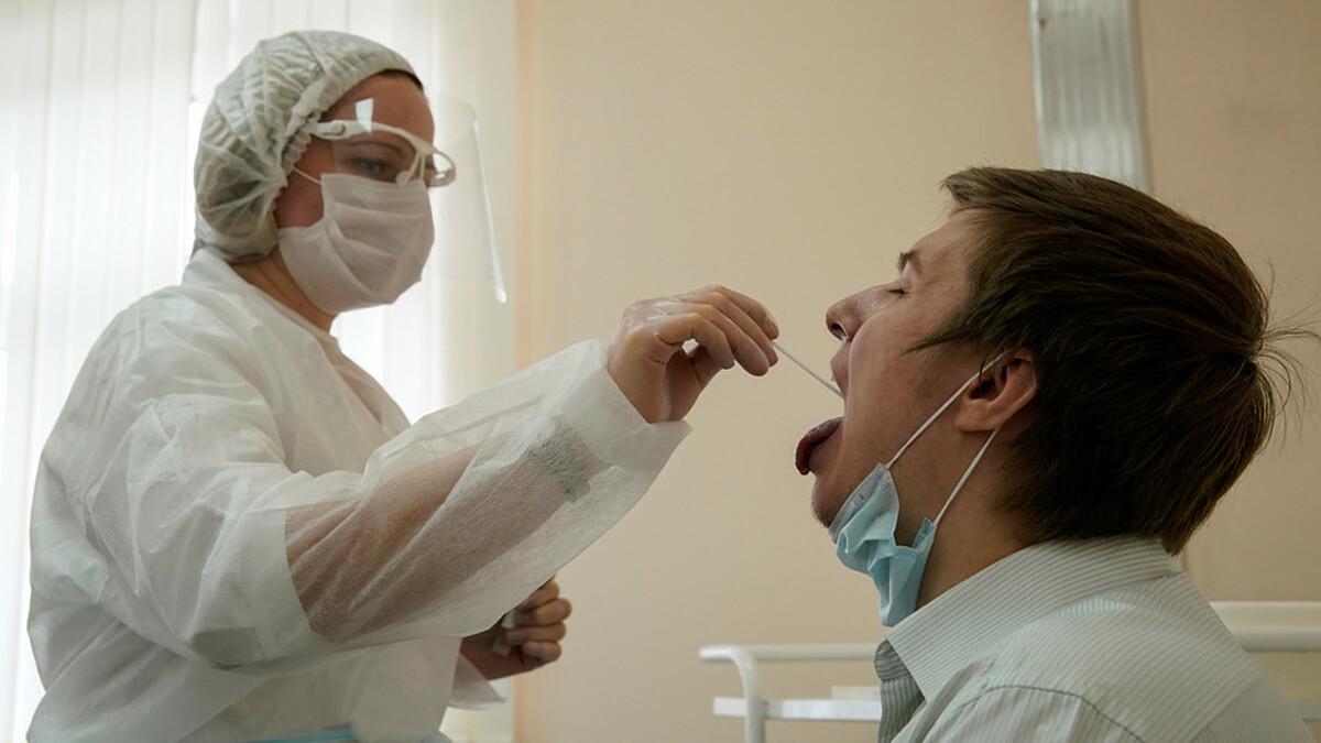 Nhân viên y tế lấy mẫu dịch ngoáy họng của bệnh nhân để xét nghiệm nCoV tại Moskva. Ảnh: Reuters