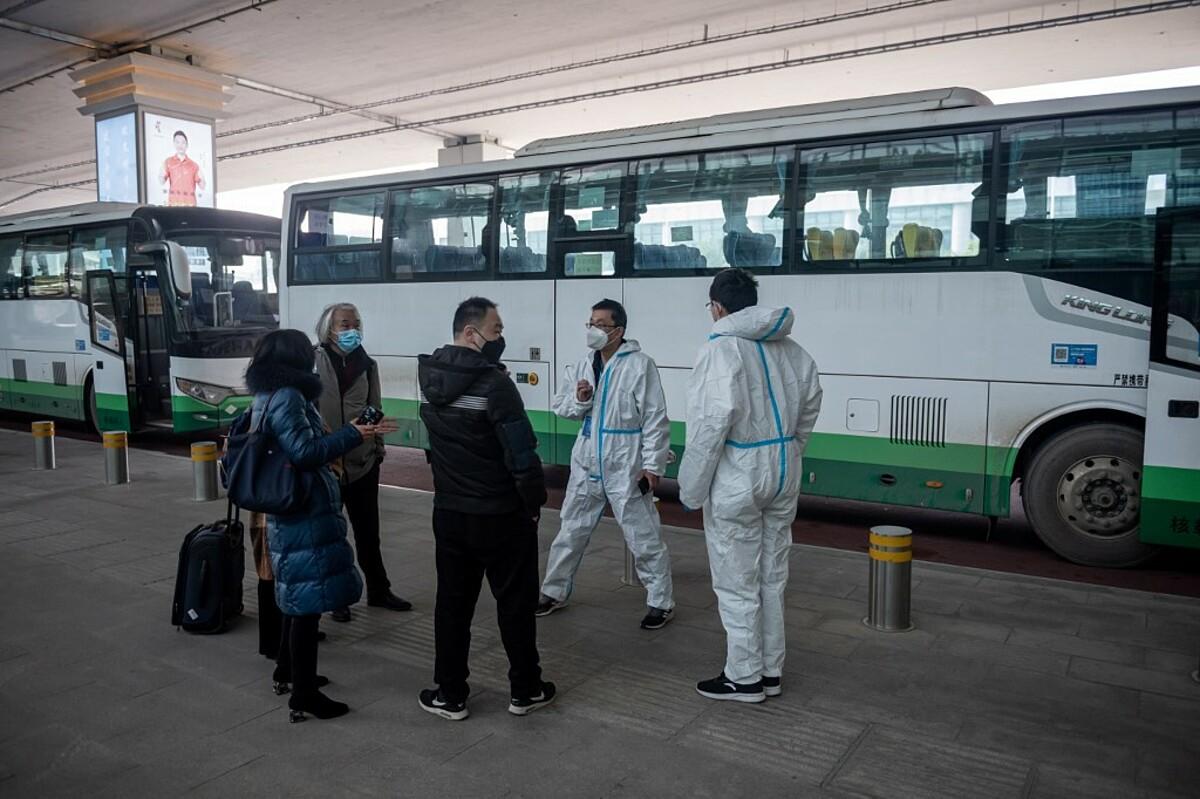 Các chuyên gia của WHO được nhân viên y tế hộ tống ở sân bay Vũ Hán, ngày 14/1. Ảnh: AFP