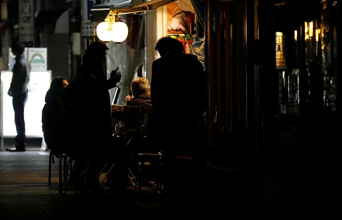 Người dân Tokyo uống rượu bên ngoài một quán bar mở cửa sau 8 giờ tối, trái quy định chính phủ, ngày 15/1. Ảnh: Reuters