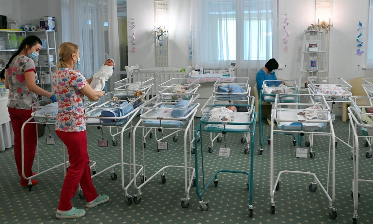 Y tá chăm sóc cho trẻ sơ sinh vừa ra đời nhờ mang thai hộ tại khách sạn Venice ở Kiev, Ukraina, tháng 5/2020. Ảnh: VCG
