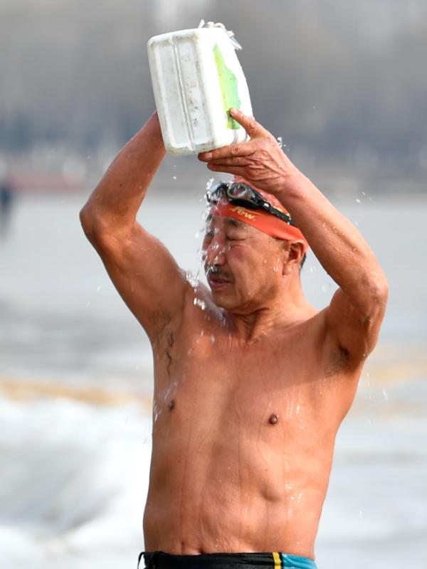 Ông Wang tắm tráng trước khi đầm mình xuống làn nước giá lạnh. Ảnh: China Daily.