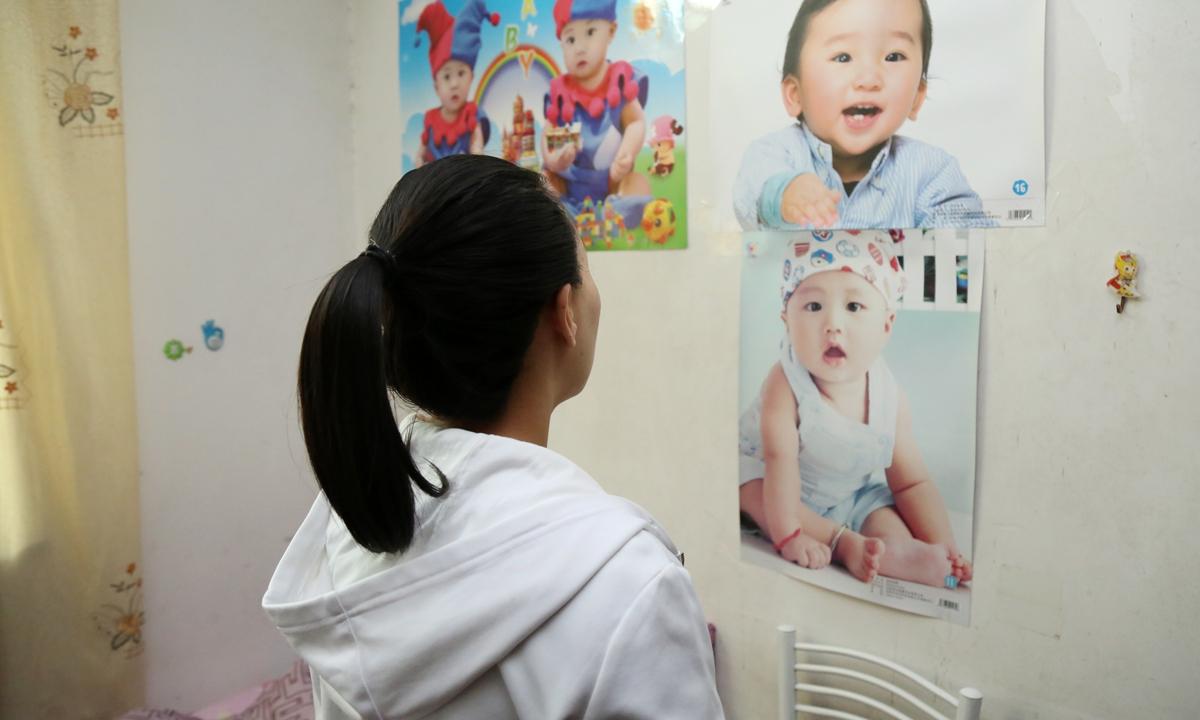 Một bà mẹ mang thai hộ ở Thượng Hải nhìn tấm ảnh của đứa trẻ cô đã sinh ra. Ảnh: IC