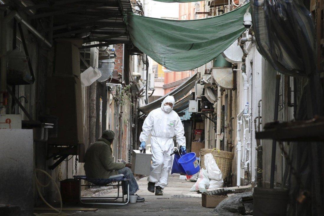 Nhân viên xét nghiệm thu thập mẫu nước thải tại một khu dân cư thuộc quận Jordan, Hong Kong. Ảnh: SCMP