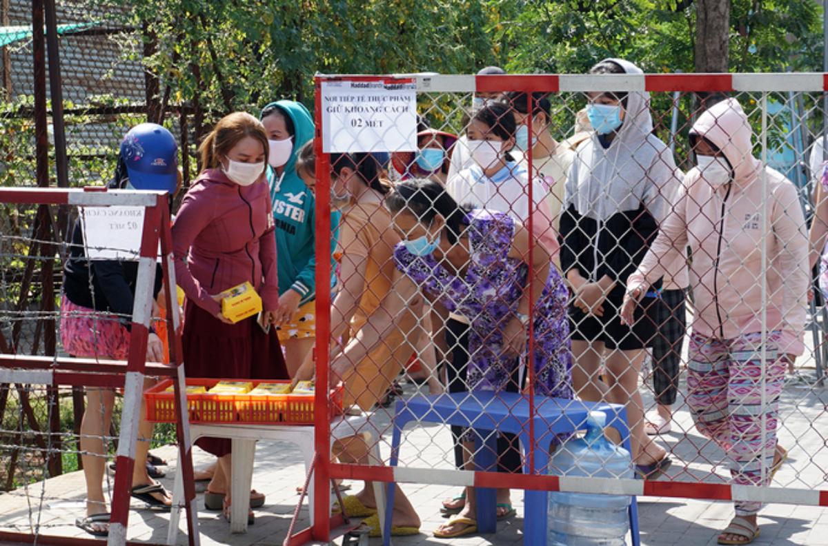Người dân trong khu cách ly ở TP Thủ Dầu Một nhận đồ tiếp tế, ngày 2/2. Ảnh: Nguyệt Triều.