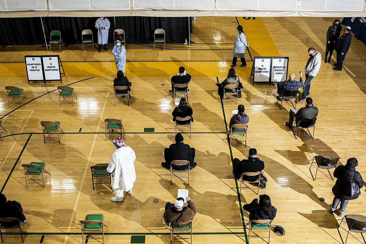 Người dân tại một điểm tiêm chủng ở Newark, Mỹ, chờ đợi 15 phút sau khi tiêm vaccine để phòng phản ứng phụ. Ảnh: WSJ