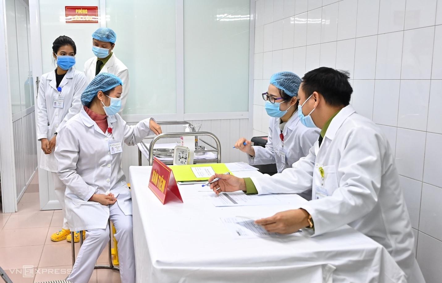 Nhân viên y tế tại Học viện Quân y chuẩn bị khám lâm sàng cho người tiêm thử vaccine Nanocovax. Ảnh: Giang Huy.