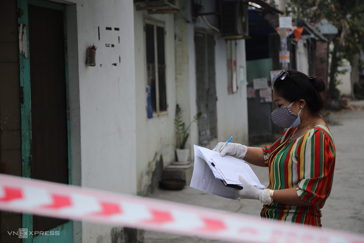 Nhân viên y tế quận 12 đến từng nhà để phát tờ khai y tế, sáng 8/2. Ảnh: Đình Văn.