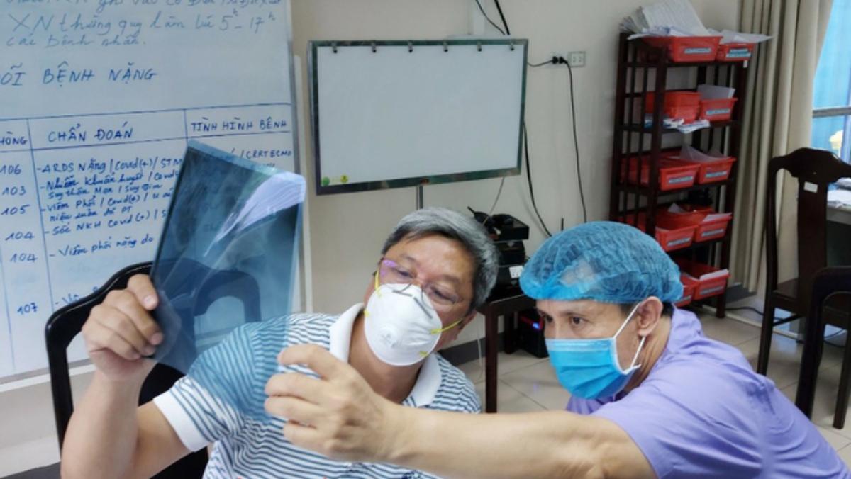 Thứ trưởng Y tế Nguyễn Trường Sơn (áo kẻ) kiểm tra phim X-quang của bệnh nhân Covid-19 tại Bệnh viện Trung ương Huế. Ảnh: Văn Anh.