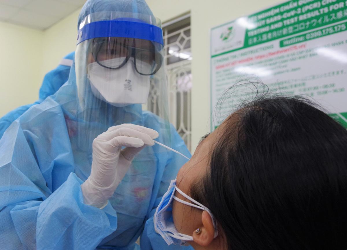 Nhân viên y tế lấy mẫu nhân viên y tế Bệnh viện Quân y 175 tối 8/2. Ảnh: Trần Chính.