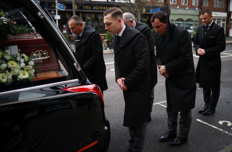 Những người khiêng quan tài của W. Uden & Sons cúi đầu trước linh cữu. Ảnh: Reuters.
