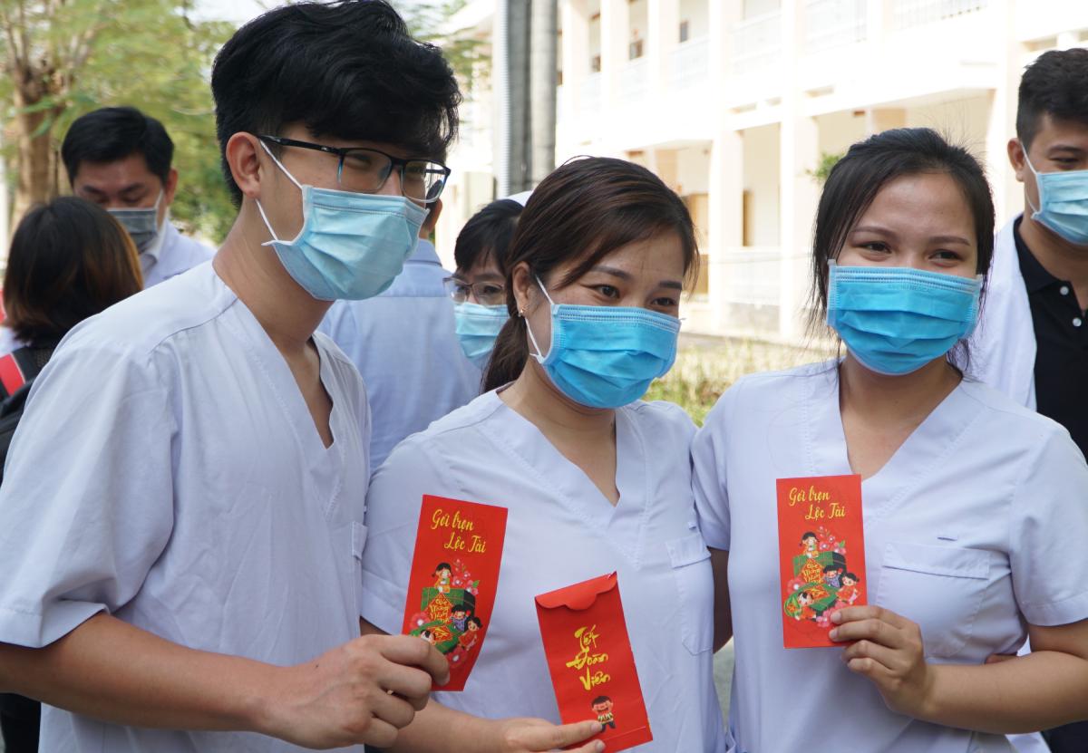 Điều dưỡng Trang (ở giữa) và các đồng nghiệp khoe phong bao lì xì đỏ được Thứ trưởng Y tế Nguyễn Trường Sơn tặng sáng 30 tết. Ảnh: Thư Anh.