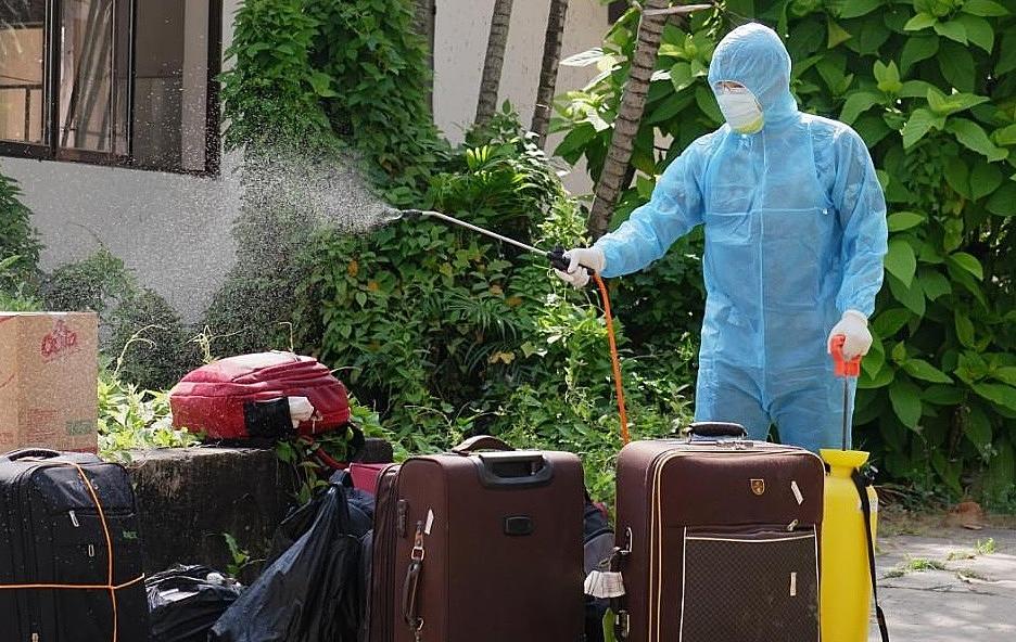 Hành lý hành khách được khử khuẩn trước khi đưa vào khu cách ly tập trung ngày 30 Tết. Ảnh: HCDC.