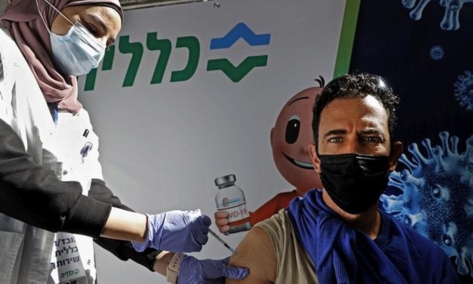Nhân viên y tế tiêm vaccine Covd-19 của Pfizer/BioNtech cho người dân tại thành phố Petah Tikva, Israel hôm 1/2. Ảnh:AFP.