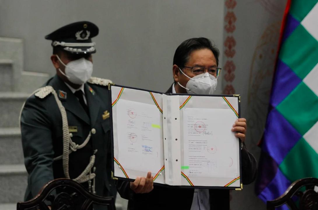Tổng thống Bolivia Luis Arce (phải) cầm hợp đồng mua vaccine của hãng dược Sinopharm Trung Quốc, ngày 11/2. Ảnh: Xinhua