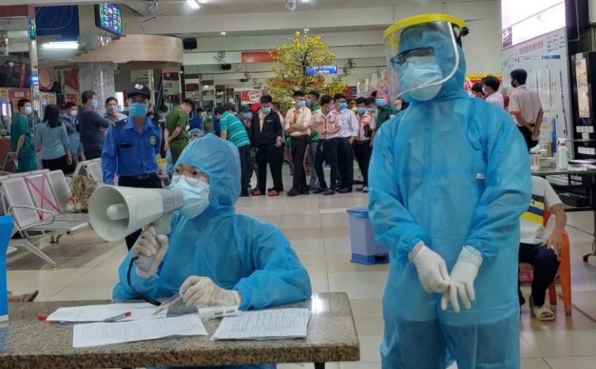 Cán bộ y tế thuộc Trung tâm y tế Quận Bình Thạnh lấy mẫu xét nghiệm cho hàng trăm người là nhân viên xếp dỡ, nhân viên bán vé, bảo vệ, tài xế và hành khách có mặt tại bến xe Miền Đông (cũ) tối 30 tết. Ảnh: HCDC.
