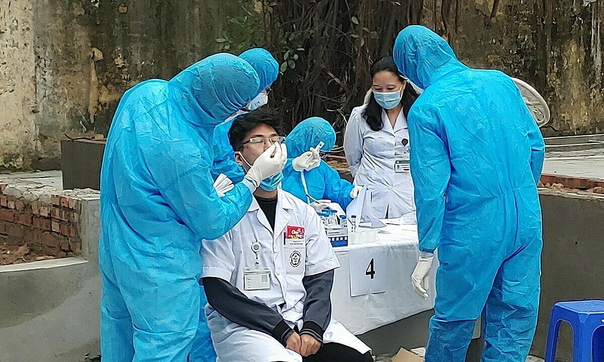 Nhân viên y tế Bệnh viện Bạch Mai lấy mẫu xét nghiệm nCoV sau kỳ nghỉ Tết. Ảnh: Thế Anh.