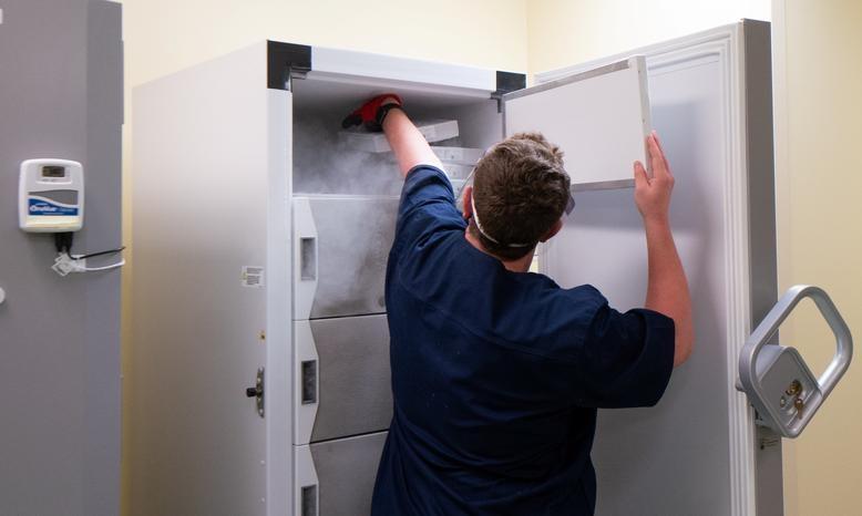 Dược sĩ Nikolas Gardner đặt một khay vaccine Pfizer-BioNTech vào tủ đông ở bệnh viện tại thành phố Madison, bang Wisconsin, hôm 14/12.