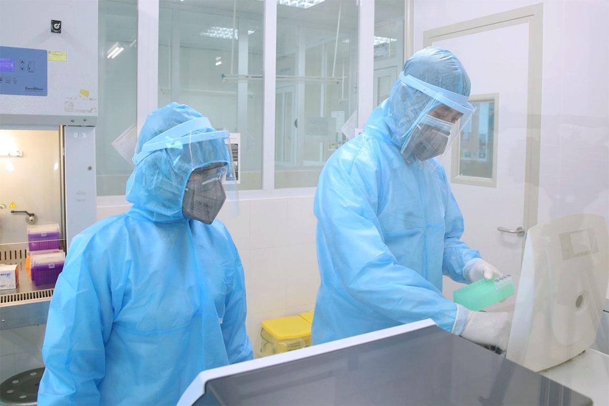 Cán bộ y tế phân tích mẫu bệnh phẩm liên quan đến cô gái về từ huyện Cẩm Giàng, Hải Dương. Ảnh: Tuấn Dũng