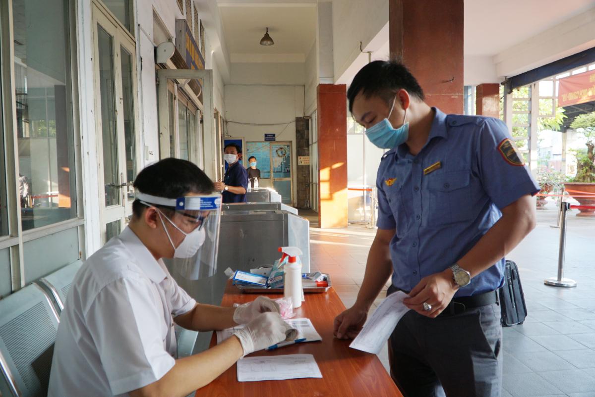 Anh Đạt (bên trái) dán mã code vào phiếu khai báo và ống lưu bệnh phẩm cho người lấy mẫu xét nghiệm. Ảnh: Thư Anh.