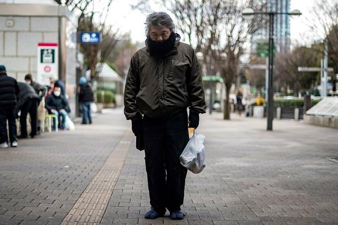 Một người nghèo Nhật Bản xách túi đồ ăn nhận được từ Trung tâm Hỗ trợ Moyai ở quận Shijuku, Tokyo. Ảnh:Japan Times.