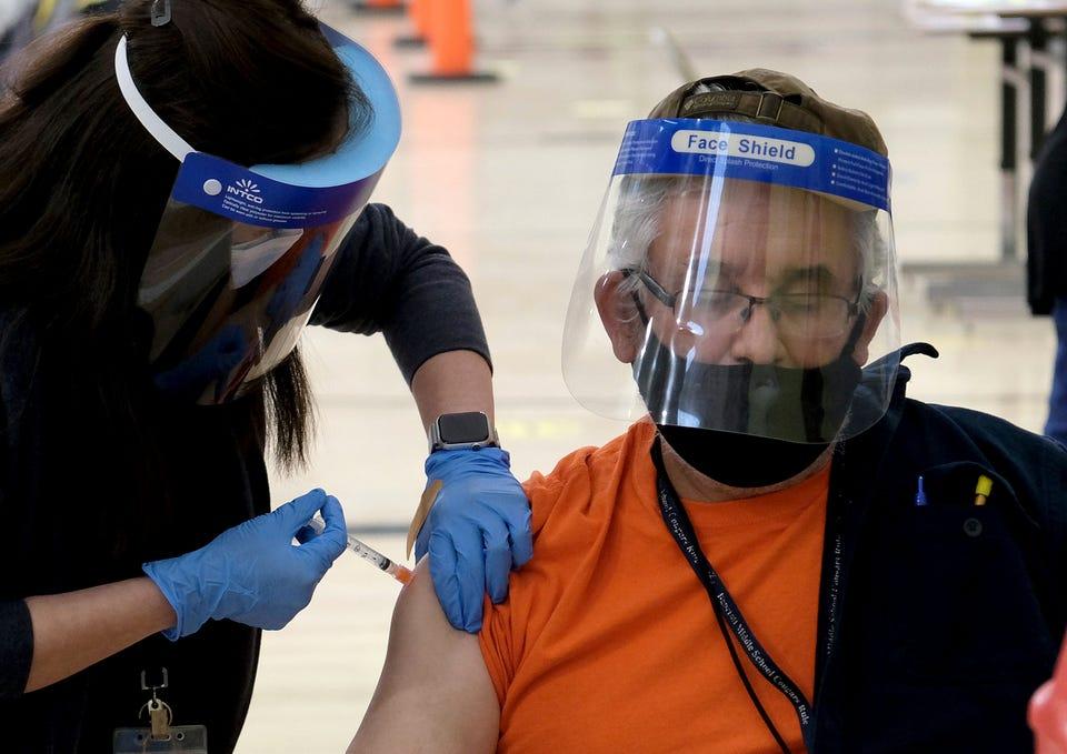 Ông Raymundo Armagnac, làm việc tại trường tiểu học Denker, gần Los Angeles, đang được tiêm liều vaccine Moderna đầu tiên vào ngày 17/2. Ảnh: USA Today.