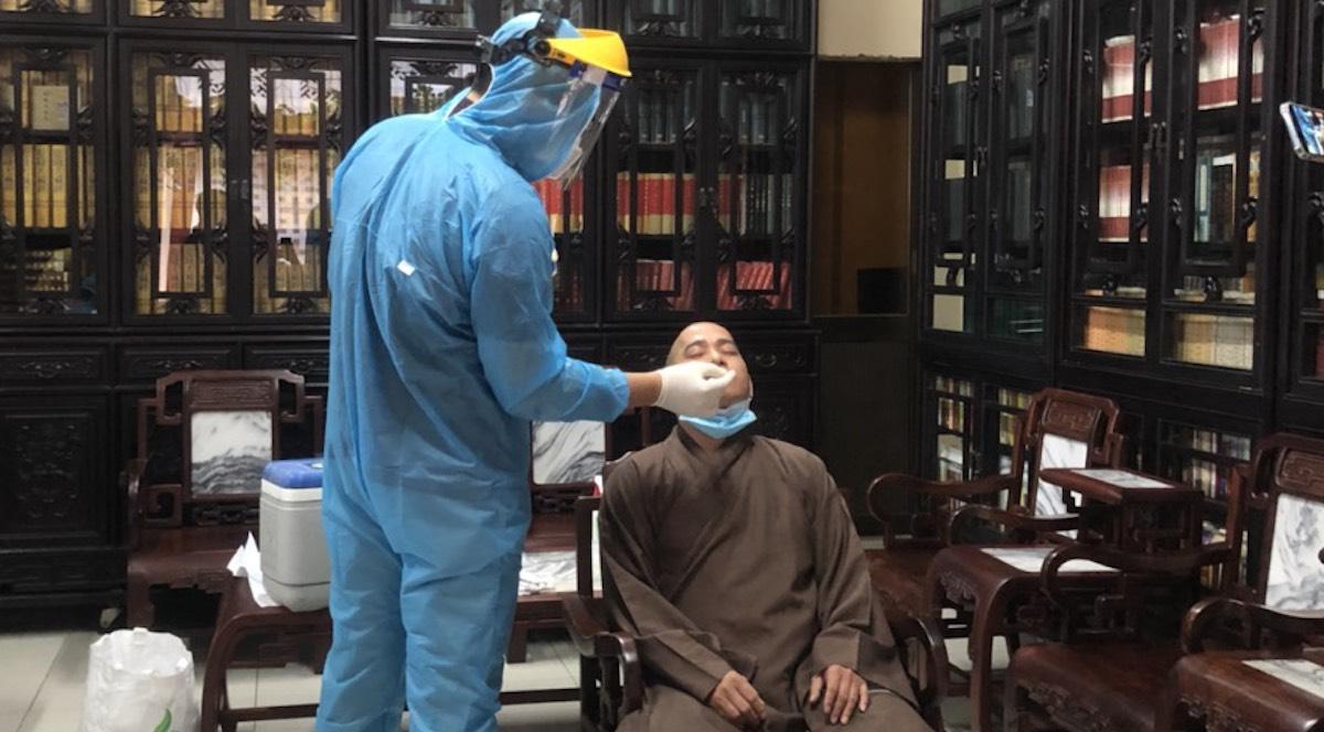Nhân viên y tế quận Tân Bình lấy mẫu xét nghiệm cho thành viên Ban trị sự chùa Viên Giác. Ảnh: