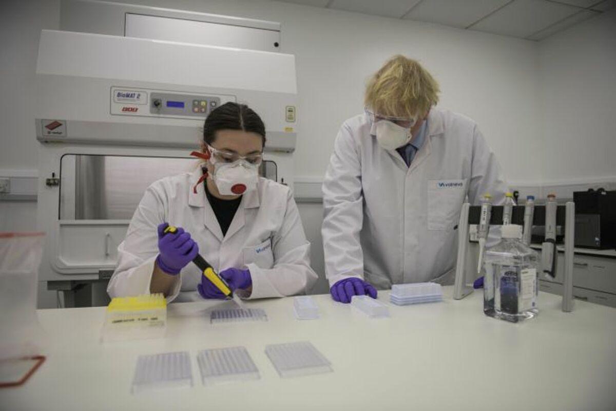 Thủ tướng Anh Boris Johnson (phải) cùng kỹ thuật viên kiểm soát chất lượng vaccine tại phòng thí nghiệm ở Scotland, ngày 28/1. Ảnh: AP