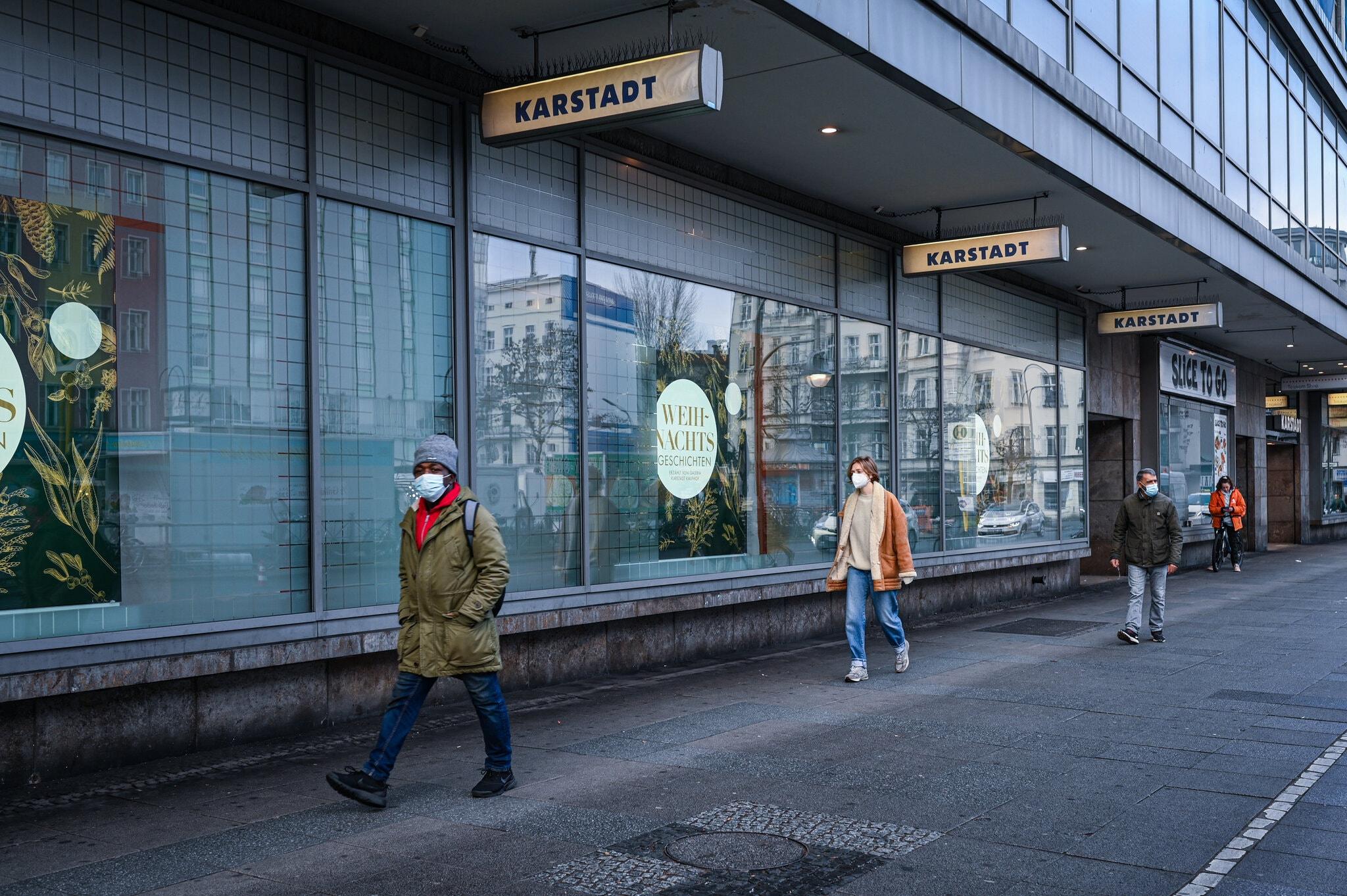 Người dân đi bộ bên ngoài các cửa hàng bị đóng ở Berlin. Ảnh: NY Times