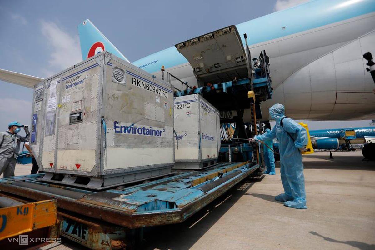 Các kiện vaccine Covid-19 đầu tiên về đến sân bay Tân Sơn Nhất sáng 24/2, được khử khuẩn sau khi ra khỏi máy bay. Ảnh: Hữu Khoa.