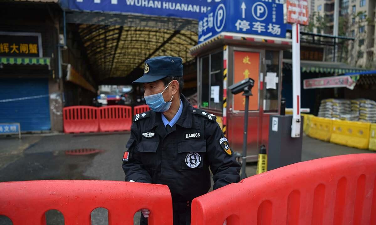 Một nhân viên bảo an đứng giám sát bên ngoài chợ hải sản Hoa Nam. Ảnh: AFP