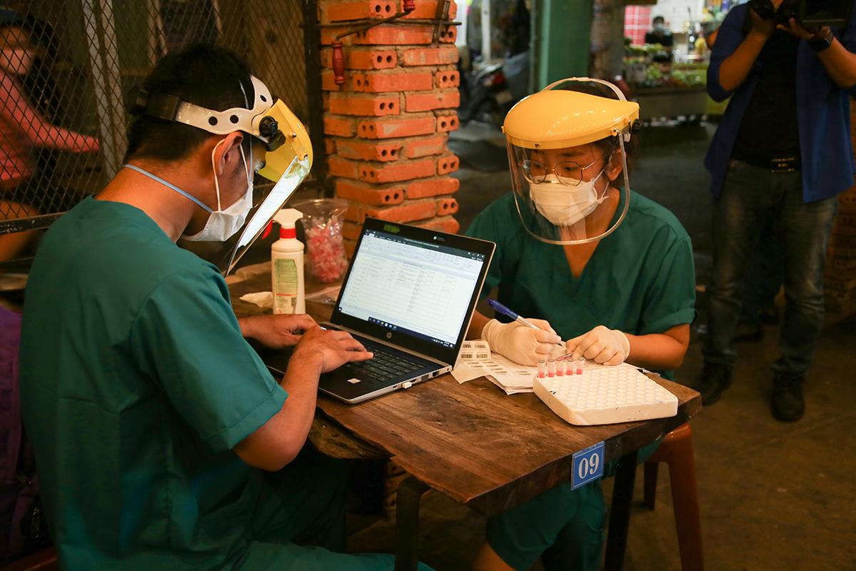 Nhân viên y tế nhập thông tin người được lấy mẫu vào phần mềm giám sát dịch bệnh tối 22/2.
